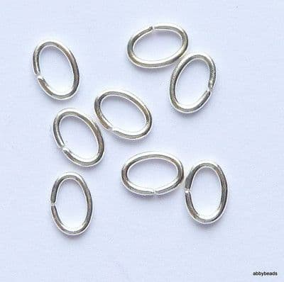 "Oval jump rings 7 X 5 x 0.9mm wire Silver plated on brass wire ""open"". Per 100."