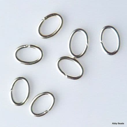 "Oval jump rings 6 x 4 x 0.9 mm. Silver plated on Brass wire ""open""  Per 100"